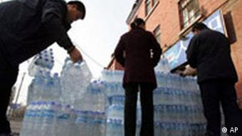 Workers load bottled water in Harbin, China (Photo: AP Photo/Greg Baker)