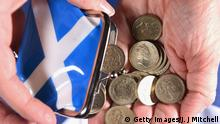 GLASGOW, SCOTLAND - AUGUST 20: In this photo illustration, pound coins are shaken from a purse on August 20, 2014 in Glasgow,Scotland. First Minister Alex Salmons, chief economic adviser has insisted Scotland has viable options for its currency if there is a yes vote in the independence referendum on September the18th. (Photo by Jeff J Mitchell/Getty Images)