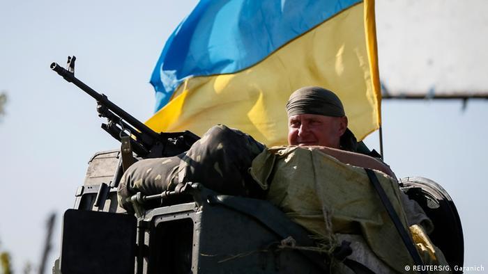 Ukrainischer Soldat vor der Flagge (Foto: Reuters)