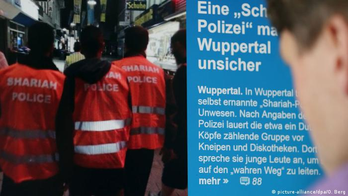 men wearing vests that read Scharia Polizei Photo: Oliver Berg/dpa