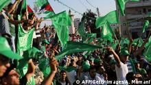 Palestinian supporters of the Islamist movement Hamas wave national and Hamas flags during a rally in the West Bank city of Ramallah on August 30, 2014. Last week, Hamas and Israel agreed an Egypt-mediated ceasefire to end a deadly 50-day war with Israel in Gaza that killed more than 2,100 Palestinians. AFP PHOTO / ABBAS MOMANI (Photo credit should read ABBAS MOMANI/AFP/Getty Images)
