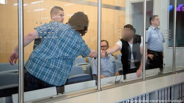 Accused Marco G. (r.) (face disguised) greets a fellow defendant at the trial. Photo: Federico Gambarini/dpa
