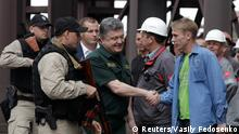 Ukrainian President Petro Poroshenko (C) shakes hands with a worker during his visit to the Ilyich Iron and Steel Works in the southern coastal town of Mariupol September 8, 2014. Poroshenko visited the eastern Ukrainian port of Mariupol on Monday in a show of solidarity with its embattled citizens and vowed to defend it from pro-Russian separatists who advanced towards it last week before a ceasefire agreement. REUTERS/Vasily Fedosenko (UKRAINE - Tags: CIVIL UNREST POLITICS BUSINESS INDUSTRIAL PROFILE TPX IMAGES OF THE DAY CONFLICT)