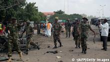 Military officers walk at a scene where a bomb exploded on July 23, 2014 in Kaduna, north of Nigeria. A second blast today in the city has killed at least 17 people, the national rescue agency said, after an earlier suicide attack in the city killed at least 25. An around-the-clock curfew was announced for the city after the bombings. AFP PHOTO / STRINGER (Photo credit should read -/AFP/Getty Images)