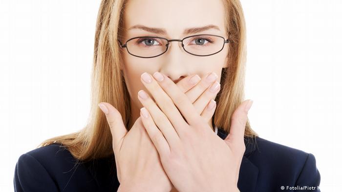 Eine Frau hält sich beide Hände vor den Mund