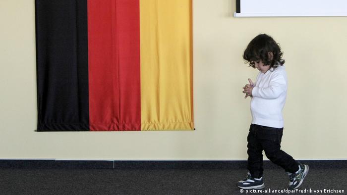 Ребенок из семьи сирийских беженцев на фоне флага Германии