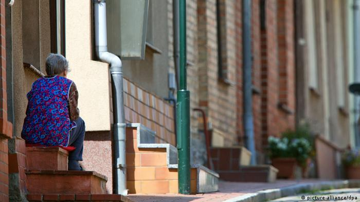 Idosa sentada na escada de uma casa