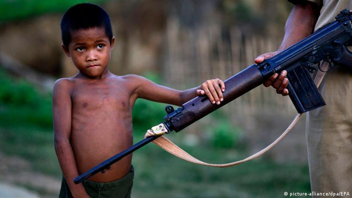 Ein kleiner Junge von vielleicht sechs Jahren hält seine kleine Hand auf das Maschinengewehr eines Soldaten, der nicht mehr ganz im Bild zu sehen ist. (Foto:picture-alliance/dpa/EPA)