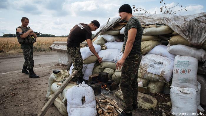 Ukrainische Soldaten richten sich hinter hohen Sandsack-Sperren ein (foto: dpa)