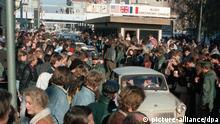 Die ersten Trabis werden am 10.11.1989 am Berliner Grenzübergang Checkpoint Charlie von unzähligen Menschen begrüßt. Nach der Öffnung eines Teils der deutsch-deutschen Grenzübergänge in der Nacht vom 9. auf den 10.11.1989 reisten hunderttausende DDR-Bürger zu einem kurzen Besuch nach West-Berlin und in die Bundesrepublik Deutschland.