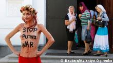 An activist of Ukrainian womens' rights group Femen participates in a protest at the Kiev Pechersk Lavra monastery in Kiev, September 11, 2014. The group was protesting against the Ukrainian Orthodox Church of the Moscow Patriarchate, which supports Russian agression in Ukraine, Femen activists said. REUTERS/Valentyn Ogirenko (UKRAINE - Tags: SOCIETY CIVIL UNREST RELIGION POLITICS CONFLICT) TEMPLATE OUT