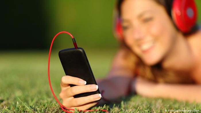 Close up of a woman with headphones holding a smart phone (Photo: Antonioguillem)