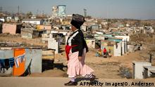A woman walks past an informal settlement in the Soweto neighbourhood of Orlando on June 28, 2013. US President Barack Obama will visit the township tomorrow as part of an African tour. AFP PHOTO / ODD ANDERSEN (Photo credit should read ODD ANDERSEN/AFP/Getty Images)