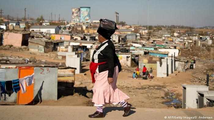 Eine Frau läuft an ärmlichen Hütten im Township Soweto vorbei