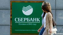 Women walk past an office of Sberbank in Moscow September 12, 2014. The United States will take new steps to limit access of major Russian banks, including Sberbank, to U.S. debt and equity markets to punish Russia for its intervention in Ukraine, sources familiar with matter said. REUTERS/Sergei Karpukhin (RUSSIA - Tags: BUSINESS POLITICS CIVIL UNREST CONFLICT)