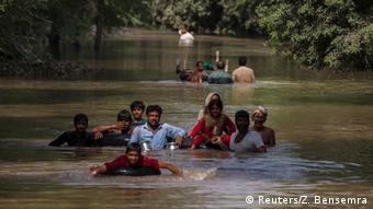 Flood victims wade through a flooded area along a road as they wait for help, in Multan, Punjab province September 13, 2014 (Photo: REUTERS/Zohra Bensemra)