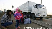 Lorries, part of a Russian humanitarian convoy, cross the Ukrainian border at the Donets'k-Izvarino custom control checkpoint as Ukrainian refugees look at them on September 13, 2014. The first 35 vehicles in a second Russian aid convoy heading for rebel-controlled eastern Ukraine have crossed the border, Russian news agencies reported. AFP PHOTO / SERGEI VENYAVSKY (Photo credit should read SERGEI VENYAVSKY/AFP/Getty Images)
