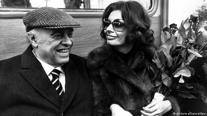 Carlo Ponti (in flatcap, striped tie and overcoat) and Sophia Loren (in fur coat and sunglasses) on a visit to Hamburg in 1975.