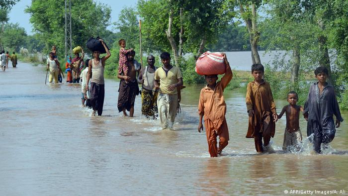 Pakistani residents wade through floodwater in Sher Shah, a town in Multan District of Punjab province on September 13, 2014 (Photo: Arif Ali/AFP/Getty Images)