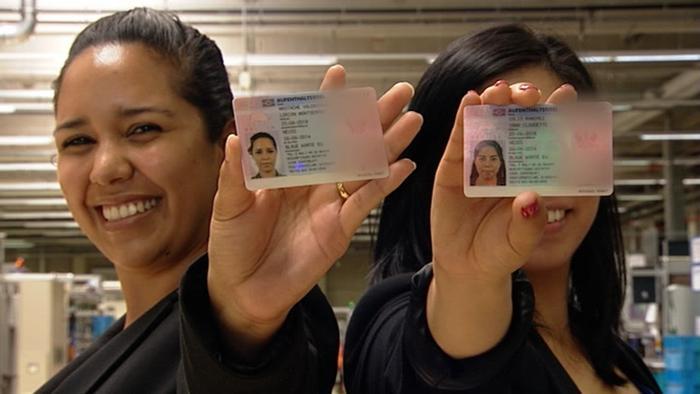 Две девушки показывают карточки, подтверждающие их вид на жительство в Германии