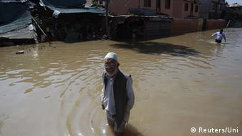 A Kashmiri man pass a damaged house as they wade through a flooded street in Srinagar September 14, 2014 (Phot: REUTERS/UNI-28R)