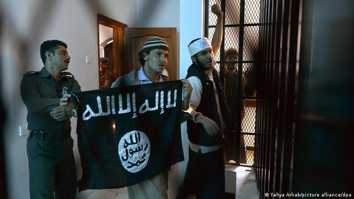 Al Qaeda supporters hold a sign saying 'no God besides Allah'