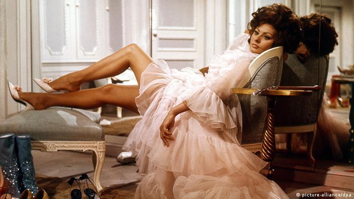 Schauspielerin Sophia Loren in einer Filmszene von Arabesque, sie räkelt sich auf antiken Stühlen in einem kurzen Kleid
