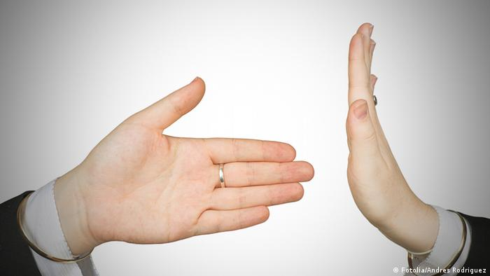 Hand extended for shaking meets hand held up in stop gesture