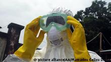 CONAKRY, GUINEA - SEPTEMBER 13: A member of a volunteer medical team wears protective glasses before burying the body of an Ebola victim died due to the Ebola virus, in the capital Conakry, Guinea on September 13, 2014. Mamadou Cellou Diallo / Anadolu Agency