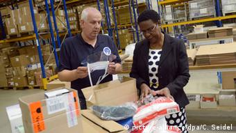 Ambassador Davis inspects aid supplies for Liberia together with Thomas Laackmann, medical director of I.S.A.R Germany