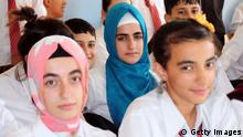 TO GO WITH AFP STORY BY FULYA OZERKAN High school students, weraing headscarves, pose on October 1, 2013 with their classmates in a Diyarbakir school. Turkey's prime minister Recep Tayyip Erdogan on October 1, 2013 announced key political reforms, including lifting a ban on Islamic headscarves and strengthening Kurdish rights. The moves come as critics accuse Erdogan of Islamising the staunchly secular country and as minority Kurds pursuing a difficult peace process with Ankara demand still more rights. AFP PHOTO/MEHMET ENGIN (Photo credit should read MEHMET ENGIN/AFP/Getty Images)