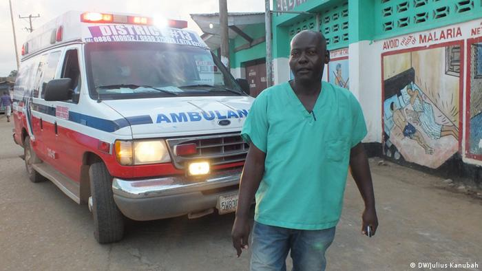 James Gbatah standing in front of an ambulance