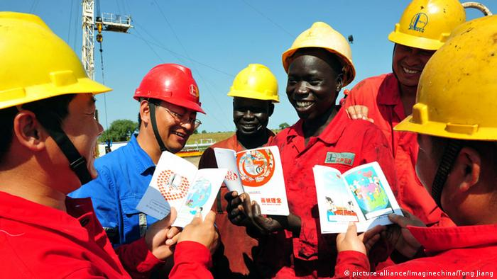 Chinese and Soputh Sudanese workers reading cartton books (picture-alliance/Imaginechina/Tong Jiang)