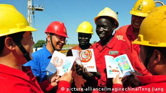 Ein chinesischer Arbeiter und seine afrikansichen Kollegen auf einem Ölfeld im Südsudan (Foto:Imaginechina)