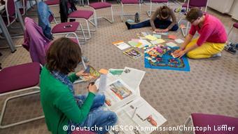 Junge Leute sitzen an einem Tisch und basteln