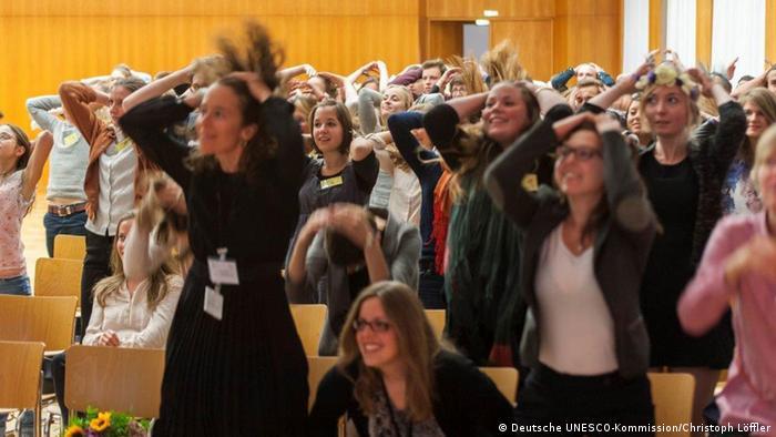Ein Raum mit jungen Leuten, die mit den Händen ihre Haare in die Luft schmeißen