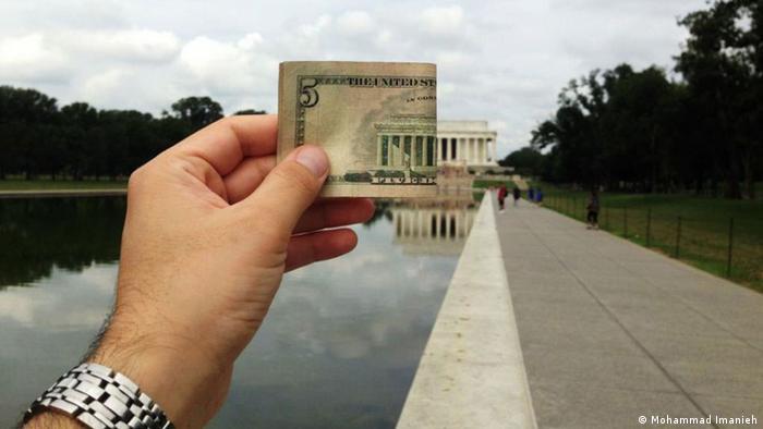 Eine Hand hält einen 5-Dollar-Schein vor das Lincoln Memorial in Washington (Mohammad Imanieh)