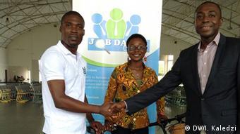 Winifred Selby (tengah) dan seorang asisten memberikan sepeda bambu kepada pembawa acara televisi Kafui Dey