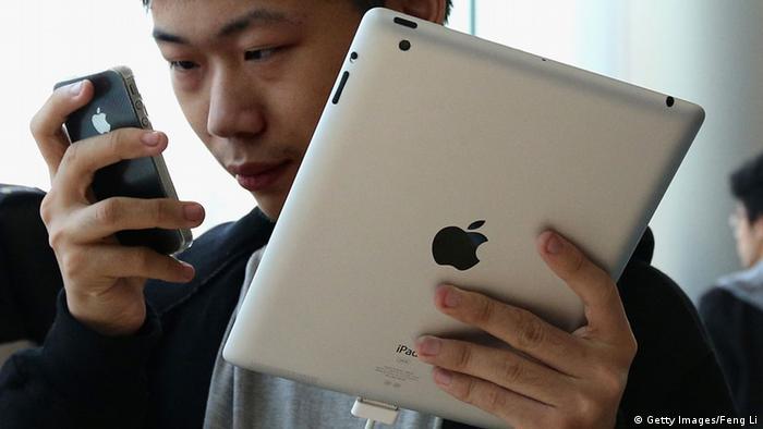 Ein Mann benutzt ein Apple iPad und ein iPhone