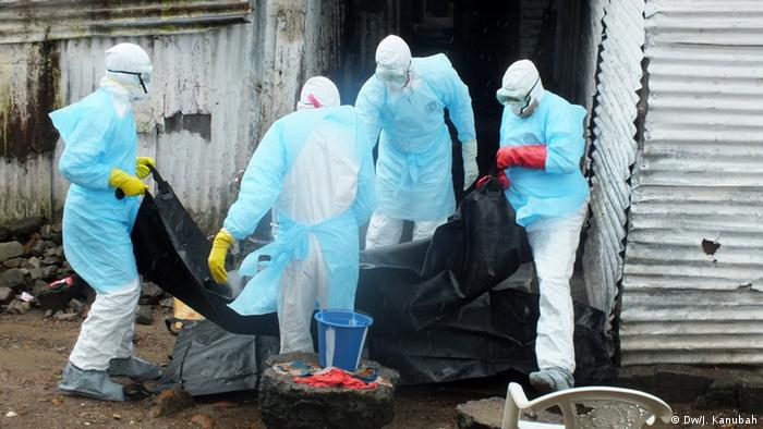 Four men in protective clothing carry a corpse in a body bag in Liberia