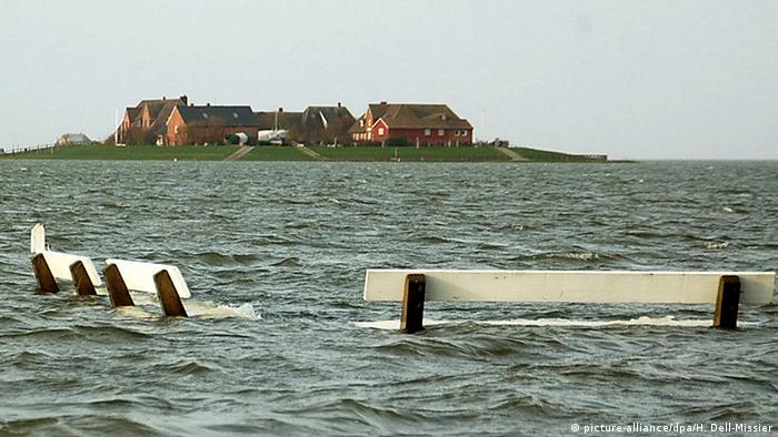 Enchente com bancos de praça inundados e casas ao fundo em parte mais alta