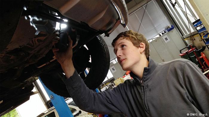 Der Auszubildende Simon Liegl vom bayerischen Autohaus Gramsamer macht einen Reifenwechsel in der Werkstatt. (Foto: DW/Gerhard Brack)