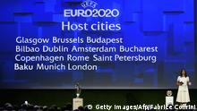 Swiss Actress and model Melanie Winiger stands by a giant screen showing the host cities of the 2020 UEFA European championship in Geneva on September 19, 2014. European football's governing body is picking 13 countries who will host football matches for the tournament. For the 60th anniversary of the European Championship, first held in 1960, UEFA decided to organise the tournament across the whole continent. AFP PHOTO / FABRICE COFFRINI (Photo credit should read FABRICE COFFRINI/AFP/Getty Images)