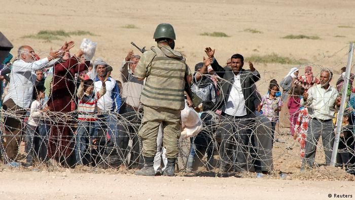 A Turkish soldier stands guard as Syrian Kurds wait behind the border fence to cross into Turkey near the southeastern town of Suruc in Sanliurfa province, September 19, 2014 (Photo: REUTERS/Stringer)