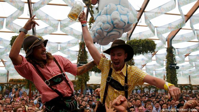 Zwei feiernde junge Männer in Tracht werden von einer Menschenmenge hochgehoben