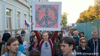 Demonstrators protest peacefully in Moscow. One holds up a peace sign on a placard.