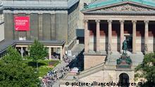 Besucher warten 23.07.2014 neben der alten Nationalgalerie in Berlin vor dem Eingang zum Pergamonmuseum. Foto: Soeren Stache/dpa