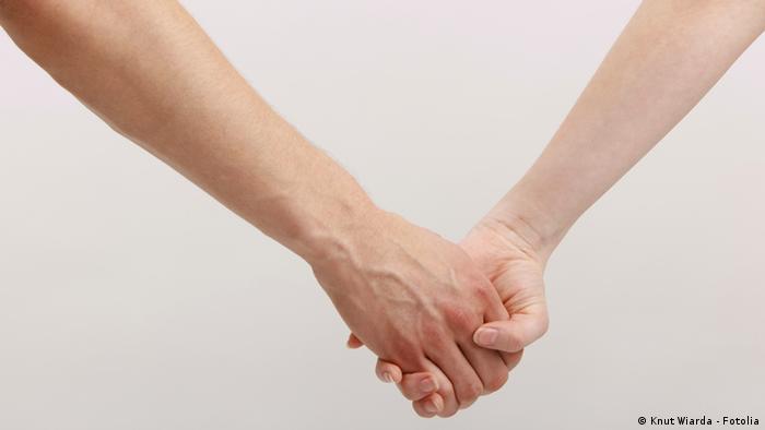 Zwei Menschen halten sich an der Hand