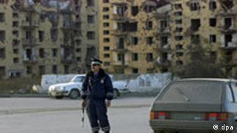 A traffic police officer guards a street in Grozny with bombed out building in the background in November 2005