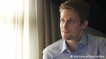 Edward Snowden sitting at a curtained window